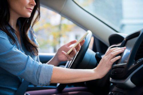 Jeune femme qui utilise le GPS de sa voiture avec son smartphone