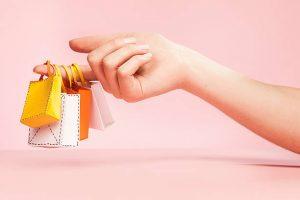 Main d'une femme tenant des sacs de shopping miniatures sur fond rose