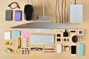 Bureau vu du dessus avec clavier, téléphone, objets connectés, stylos